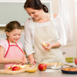 Mother and daughter cutting apples for pie - Stock Photo