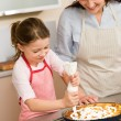 Decorating apple pie mother and daughter — Stock Photo #9548100