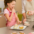 Little girl taste sprinkles decorating cupcake — Stock Photo