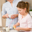 Little girl taste sprinkles cupcakes with mum — Stock Photo
