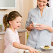 Little girl pointing cupcake to her mother — Stock Photo #9548134