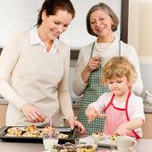 Family women baking cupcakes in kitchen — Stock Photo