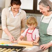 3 generations women rolling dough for baking — Stock Photo