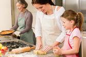 3 generations of women baking apple pies — Stock Photo