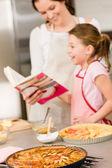 Mother and daughter look baking cookbook — Stockfoto