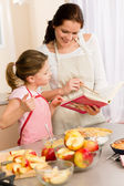 Mother and daughter look baking cookbook — Stock Photo
