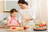 Mother and daughter cutting apples for pie — Stok fotoğraf