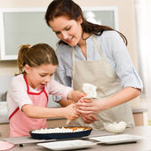 Decorating cake mother and daughter — Stock Photo