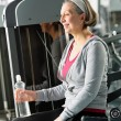 Senior woman relax sitting by fitness machine — Stock Photo