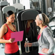 Personal trainer with senior woman at gym — Stock Photo #9624582