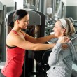 Stock Photo: Fitness center senior womexercise with trainer