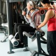 Fitness center senior woman exercise with trainer — Stock Photo