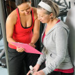 Stock Photo: Personal trainer with senior woman at gym