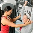Senior woman exercise on shoulder press machine - Stock Photo
