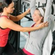 Senior woman at fitness center with trainer — Stock Photo