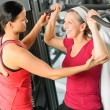 Stock Photo: Personal trainer assist senior womat gym