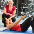 Stock Photo: Personal trainer show abdominal exercise on mat