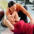 Senior woman exercise abdominal in fitness center - Stock Photo