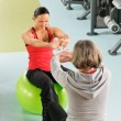 Stock Photo: Senior woman with trainer stretching fitness ball