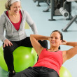 Senior woman with trainer exercising fitness ball — Stock Photo