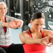 Two women at gym stretch out — Stock Photo #9624732