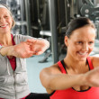 Two women at gym stretch out - Stock Photo