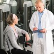 Stock Photo: Physiotherapist assist active senior womat gym