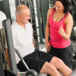 Fitness center active man exercising with trainer - Zdjcie stockowe
