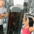 Stock Photo: Personal trainer at fitness center show exercise