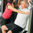 Fitness center trainer assist man exercise back - Stock Photo