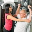 Fitness center trainer assist man exercise back - Photo