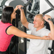 Fitness center trainer assist man exercise back — Stock Photo #9624812