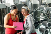 Personal trainer with senior woman at gym — Stock Photo