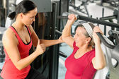 Personal trainer assist senior woman at gym — 图库照片