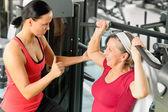 Persoonlijke trainer helpen senior vrouw op sportschool — Stockfoto