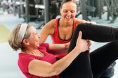 Fitness centrum starší žena vykonávat tělocvičně cvičení — Stock fotografie