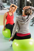Senior woman with trainer stretching fitness ball — Stock Photo
