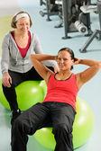 Senior vrouw met trainer uitoefening fitness bal — Stockfoto