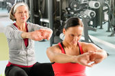 Two women at gym stretch out — Foto Stock