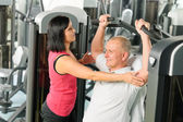 Fitness center trainer assist man exercise back — Stock Photo