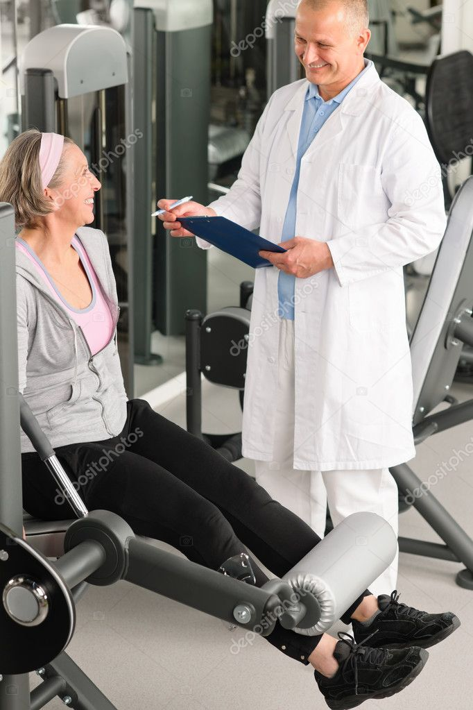 Physical therapist male assist active senior woman exercise at gym — Stock Photo #9624756