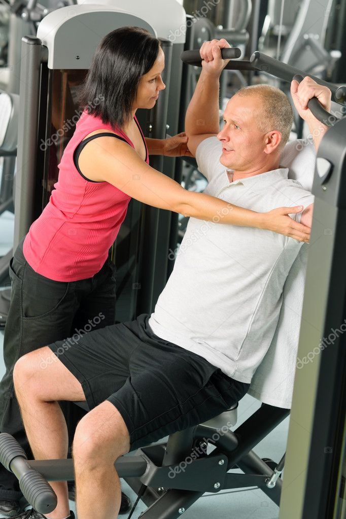 Fitness center personal trainer assist man exercise shoulder on machine — Stock Photo #9624803