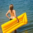 Summer woman hold yellow floating mat - ストック写真