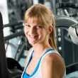 Smiling woman at fitness center exercise machine - Stock Photo