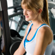 Young woman at fitness center exercise machine — Stock Photo