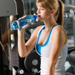 Royalty-Free Stock Photo: Woman drink water at fitness machine