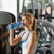 Stock Photo: Woman drink water at fitness machine