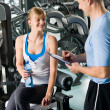 Completing personal fitness plan with trainer - Stock Photo
