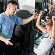 Young woman exercise on shoulder press machine — Stock Photo