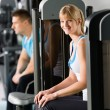 Two at fitness center exercise machine — Stock Photo #9776510